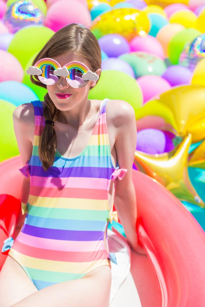 Sonnenbrille mit Regenbogen und kleinen Wolken, bunter gestreifter Badeanzug, sommerliche Stimmung