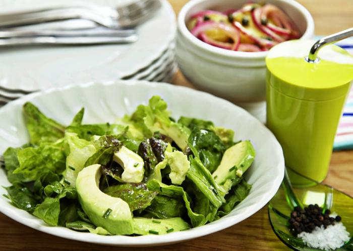 Avocado, grüne Salatblätter, mit Pfeffer und Salz gewürzt, roter Zwiebel als Dressing