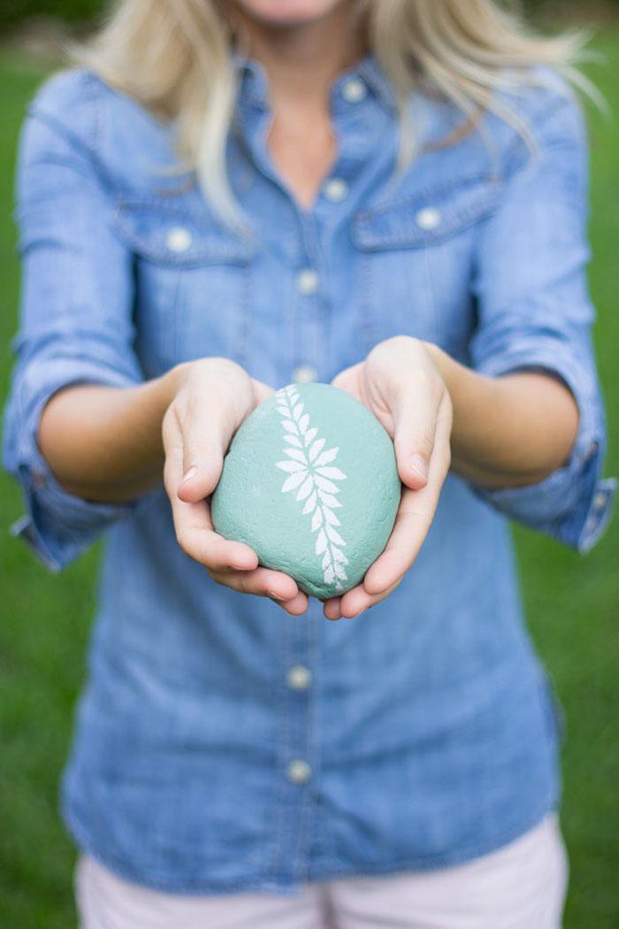 Steine mithilfe Schablonen dekorieren, weiße Blume auf grünem Grund