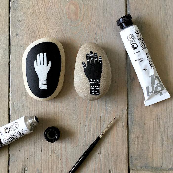 Steine mit schwarzer und weißer Acrylfarben bemalen, Hände zeichnen