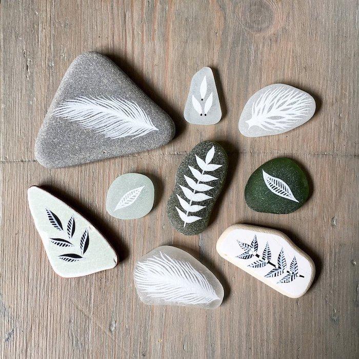 Kleine Steine selbst dekorieren, Blätter und Federn mit weißer Farbe zeichnen