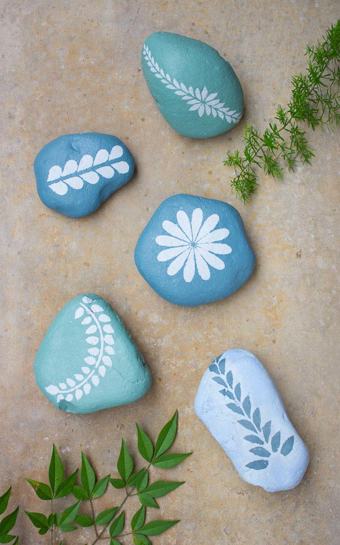 Steine bemalen, blaue Steine mit weißen Blumenmotiven, schöne Deko für den Garten