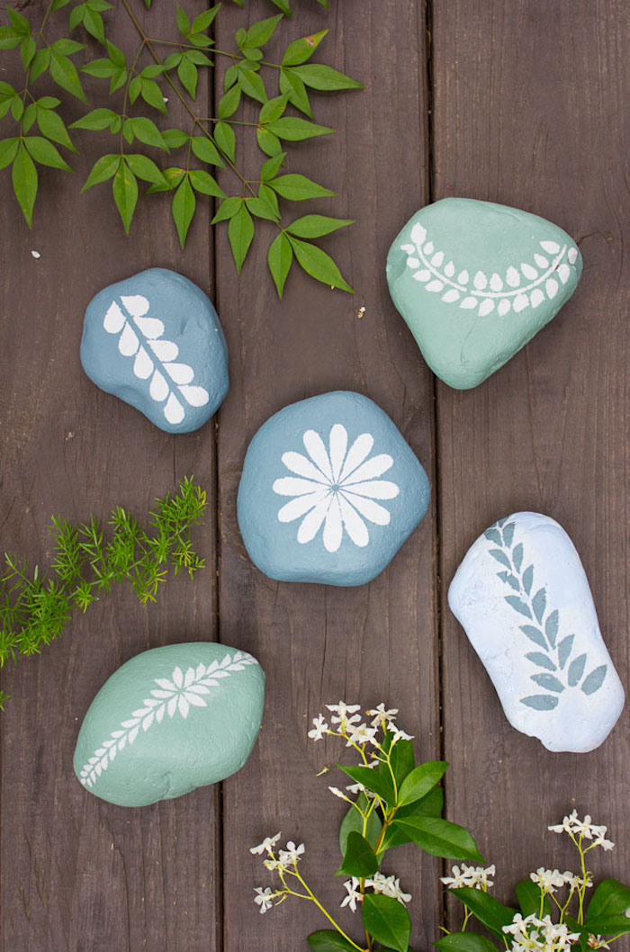 Steine mithilfe Schablonen dekorieren, weiße Blumenmotive auf grünem oder blauem Grund