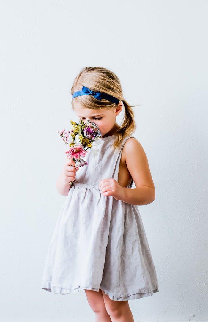 Weißes Sommerkleid, dunkelblaues Haarband, lange blonde Haare, schöner Blumenstrauß