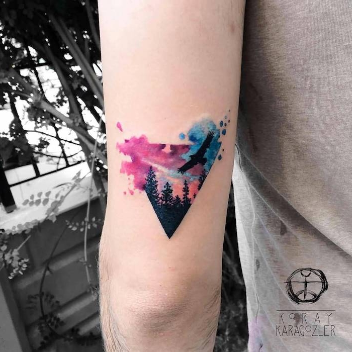 hand mit einem kleinen dreieck tattoo watercolor mit einem schwarzen fliegenden adler und einem wald mit schwarzen bäumen, vogel tattoo ideen