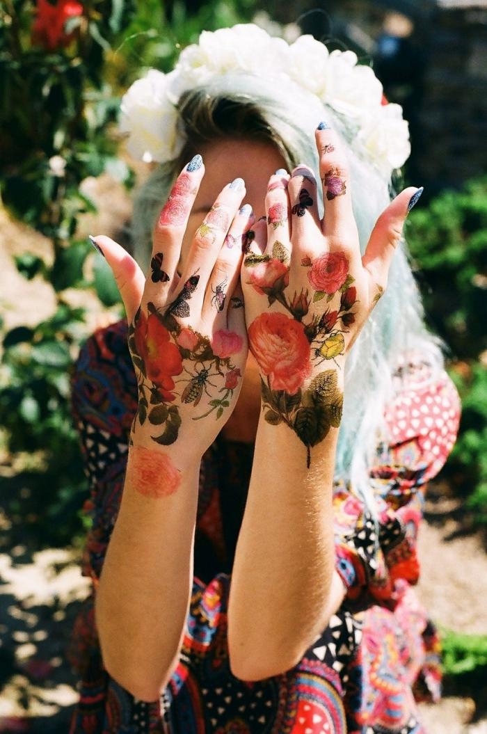 Blumen Tattoos an beiden Händen, farbige Tattoos, blauer Nagellack, buntes Sommerkleid, weißer Blumenkranz