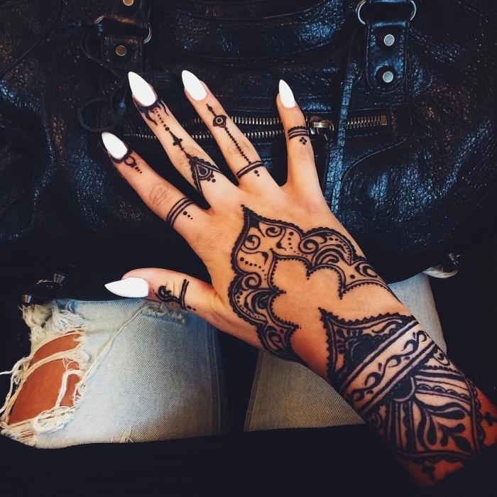 Schwarzes Henna Tattoo an der Hand, weißer Nagellack, spitze Nägel