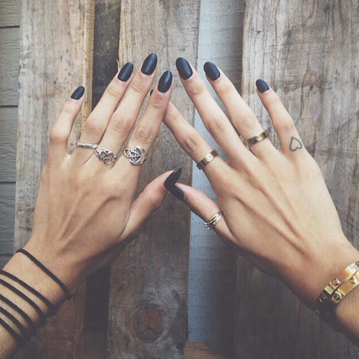 Kleines Herz Tattoo am kleinen Finger, schwarzer Nagellack, ovale Nägel, viele Ringe