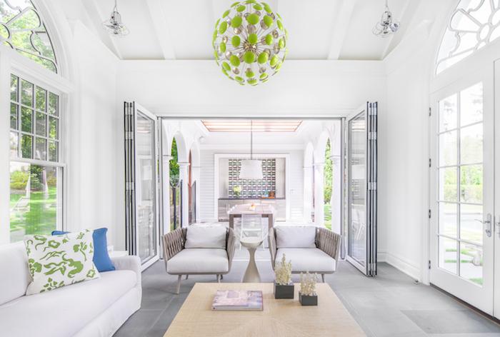 ein brauner tisch aus holz und weiße sofas mit grünen und blauen kissen udn eine große grüne lampe und eine weiße lampe