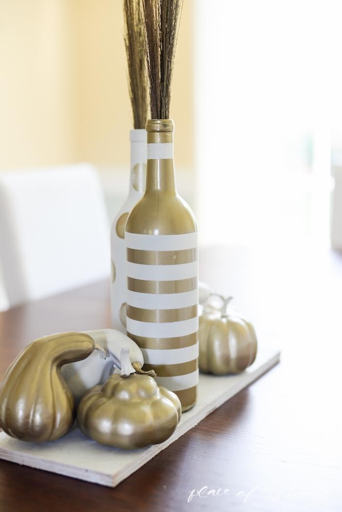 eine weiße flasche und eine goldene flasche und kleine goldene bemalte kürbisse und ein brauner tisch aus holz, eine tischdeko selber basteln