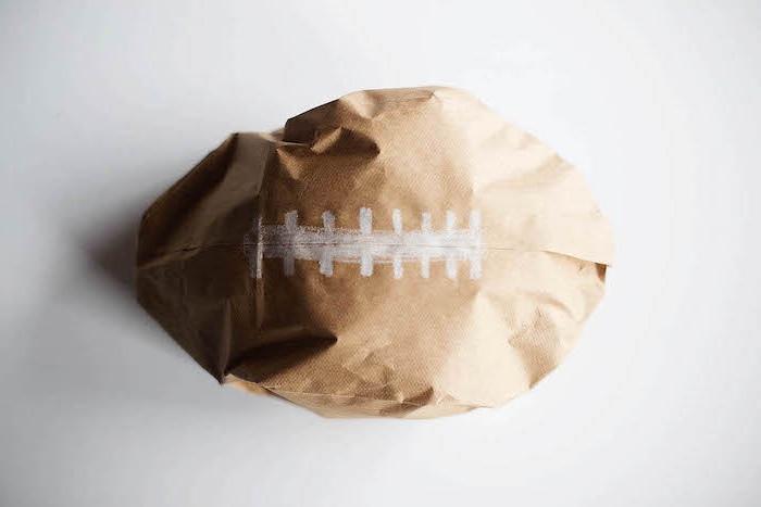 ein kleines braunes ball aus einer braunen alten papiertüte und mit einer weißen baumwolle, eine schritt für schritt diy anleitung