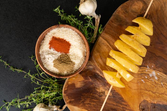 Geräucherter Paprika, Knoblauchpulver und gemahlener Kreuzkümmel in den Parmesan einrühren, die Kartoffel mit geschmolzener Butter bepinseln