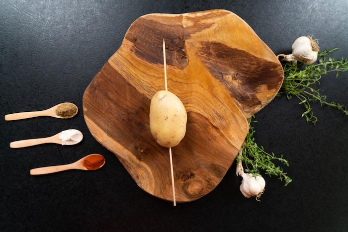 Hasselback-Kartoffeln Rezept, Holzspieß der Länge nach durch die Kartoffel stecken
