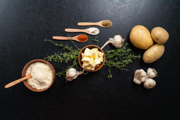 Zutaten für knusprige Hasselback-Kartoffeln, drei Kartoffeln, Butter und Parmesan, geräucherter Paprika, Knoblauchpulver und Kreuzkümmel