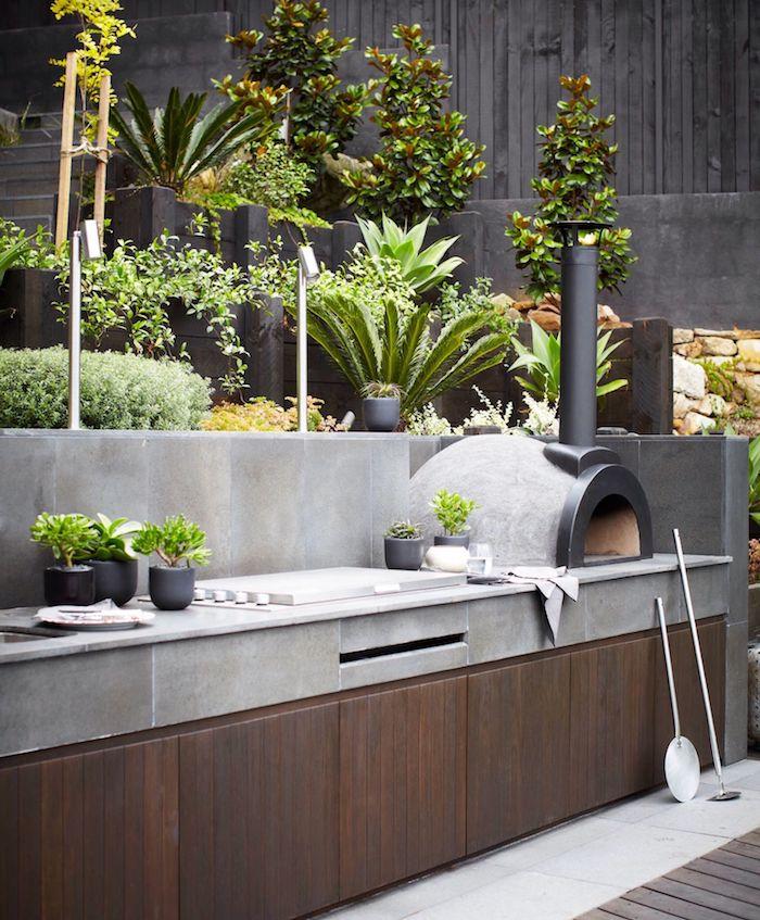 eine graue outdoor küche mit einem weißen waschbecken, ein garten mit grünen pflanzen, ein grill und kleine graue blumentöpfe