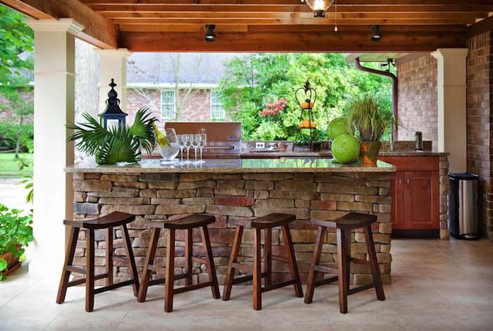 vier braune stühle aus holz und ein tisch aus steinen, gläser und grüne pflanzen, eine außenküche holz