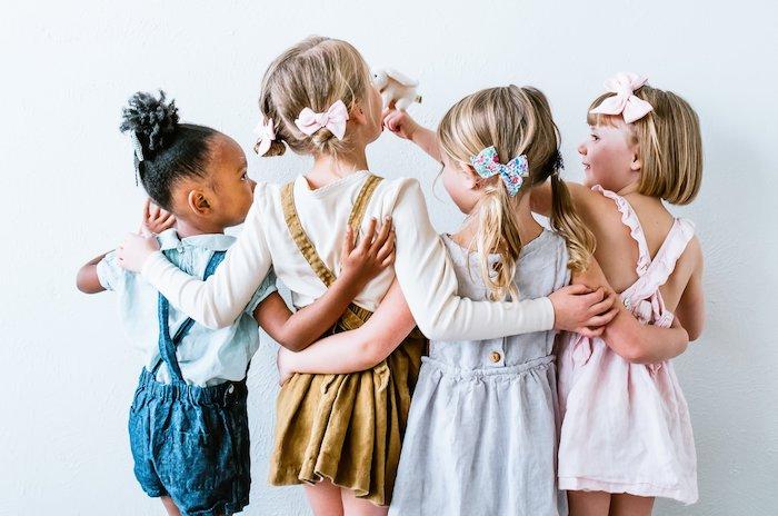 Vier Mädchen mit eleganten Outfits und schönen Frisuren, bunte Schleifen, Jumpsuits und Kleider
