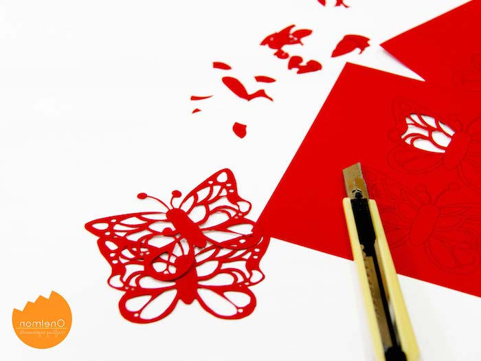 Schöne Schmetterlinge mit Cutter aus rotem Papier ausscheniden