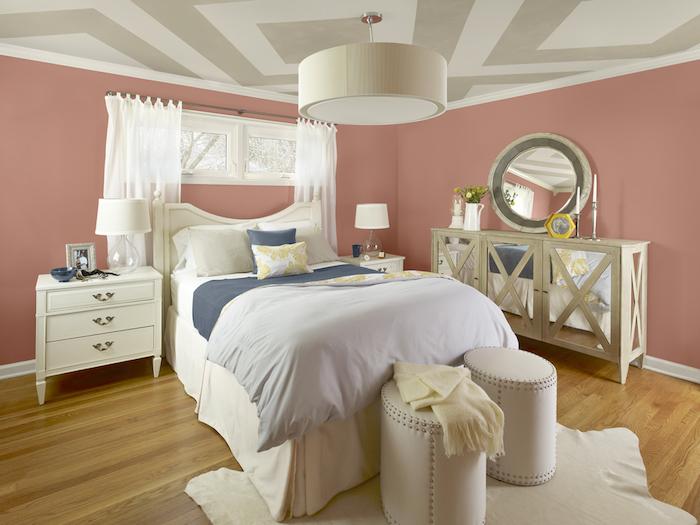 schlafzimmer mit einem bett mit kleinen weißen und grauen kissen und ein bruner boden aus holz, schlafzimmer einrichten, ein schlafzimmer mit pinken wänden