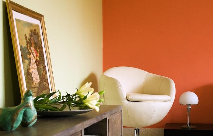 ein brauner schreibtisch aus holz und ein bild und gelbe blumen mit grünen blättern, eine kleine weiße lampe und ein weißes sofa, orange und weiße wände streichen