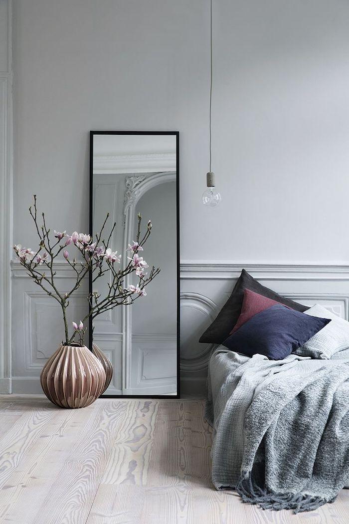 wandfarbe hellgrau, hoher spiegel mit schwarzem rahmen, geometrische vase, zweige mit kirschbütten