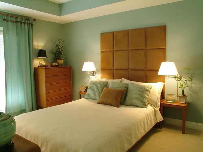 zwei weiße lampen in einem schlafzimmer mit einem bett mit einer weißen decke und braunen und grünen kissen, ein fenster mit einem grünen vorhang, blumentöpfe mit grünen pflanzen und grünen blättern