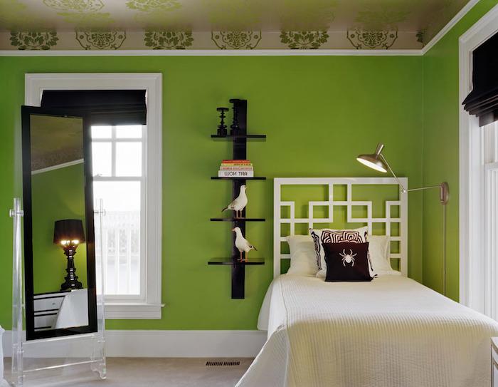 kissen mit einer weißen spinne, ein bett mit einer weißen decke, ein schlafzimmer mit einer großen grünen wand und einem spiegel und zwei kleinen weißen vögeln