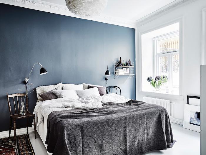 blaue große wand un einem schlafzimmer mit einem bett mit einer schwarzen decke und schwarzen und weißen kissen und einer schwarzen lampe und einem teppich