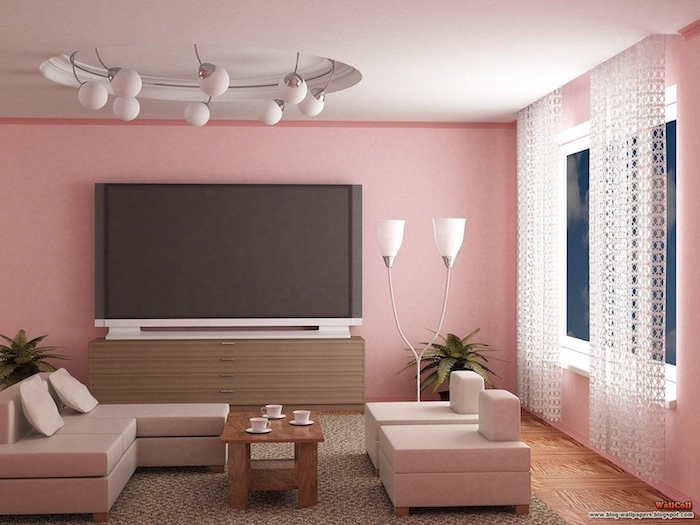 pinke wände in einem wohnzimmer mit pinken sofas mit pinken kissen und ein kleiner tisch aus holz und zwei kleine weiße lampen