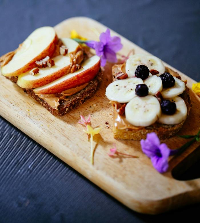 gute ernährung idee, zwei brotscheiben mit erdnussbutter, äpfel, bananen, blaubeeren, süße sandwiches