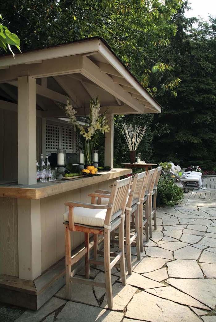 ein wald mit grünen bäumen und eine kleine außenküche mit weißen stühlen mit weißen kissen, eine vase mit weißen blumen und grünen blättern