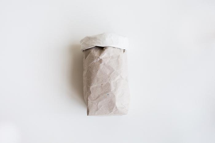 eine kleine weiße gefaltete papiertüte und ein weißer tisch, papiertüten basteln ideen