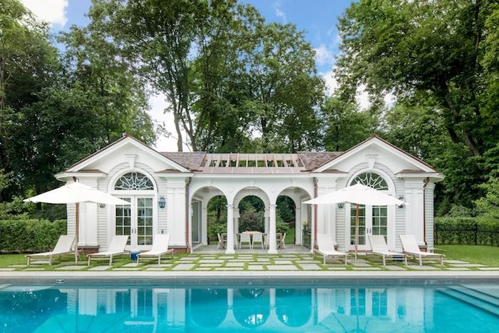 weißes haus und weiße große regenschirme und ein blaues schimmpool mit wasser in einem garten mit grünen pflanzen und grünen bäumen, eine outdoor küche bauen ideen