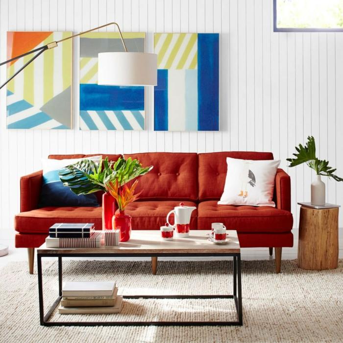 ein rotes Sofa mit bunten Kissen, bunte Bilder an der Wand, schöne Farbkombinationen