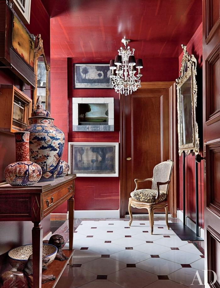 Bordeauxrote Wandfarbe, ein Barock Stuhl, ein Kronleuchter, ein Spiegel mit antiken Rahmen, welche Farbe passt zu Bordeauxrot
