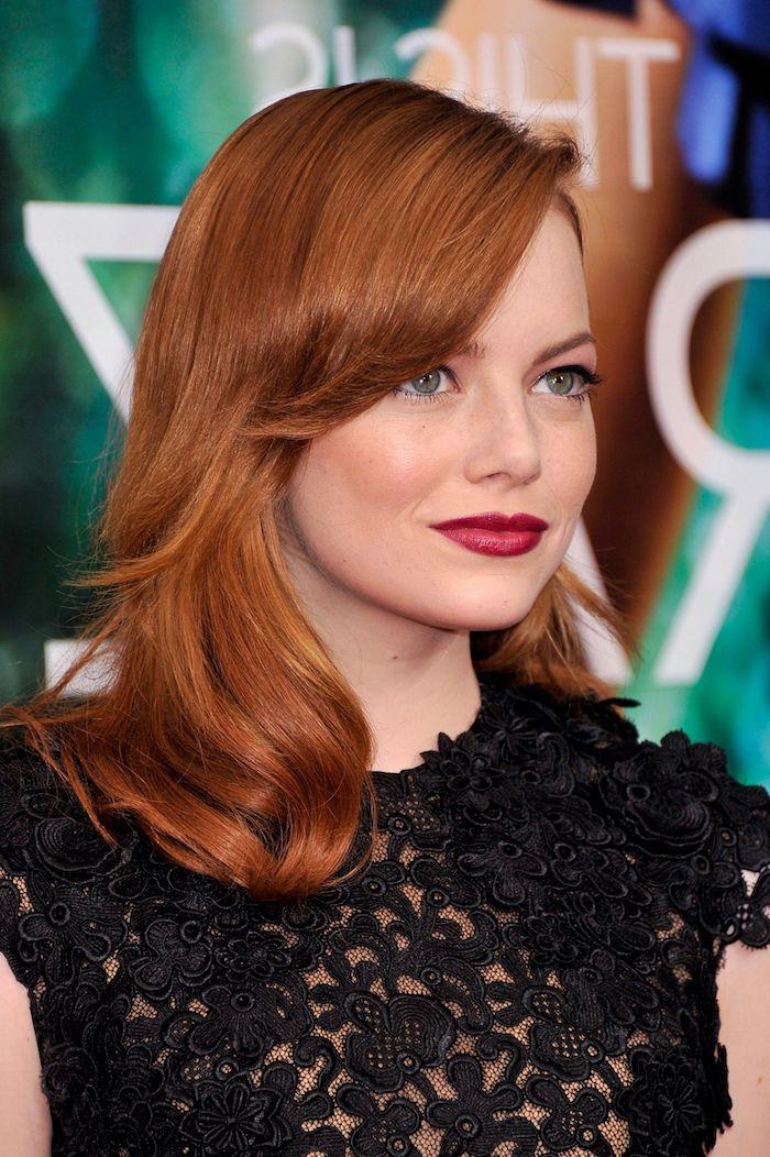 Emma Stone Haarfarbe, kupferfarbene mittellange Haare, schwarzes Spitzenkleid, roter Lippenstift und schwarzer Lidstrich