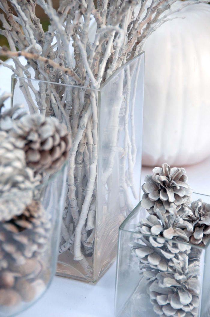 winterdeko basteln, große glasvasen in verschiedenen designs, zweige dekoriert mit weißer sprühfarbe, tannenzapfen