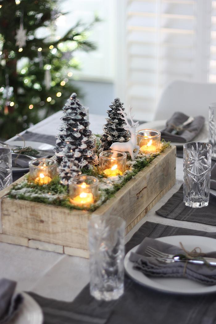winterdeko basteln, tisch dekorieren, tannenzapfen mit grünen zweigen und kerzen