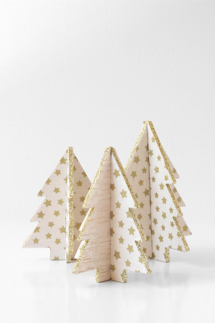 winterdeko basteln, tannenbäume aus holz dekoriert mit weißem stoff mit goldenen sternen