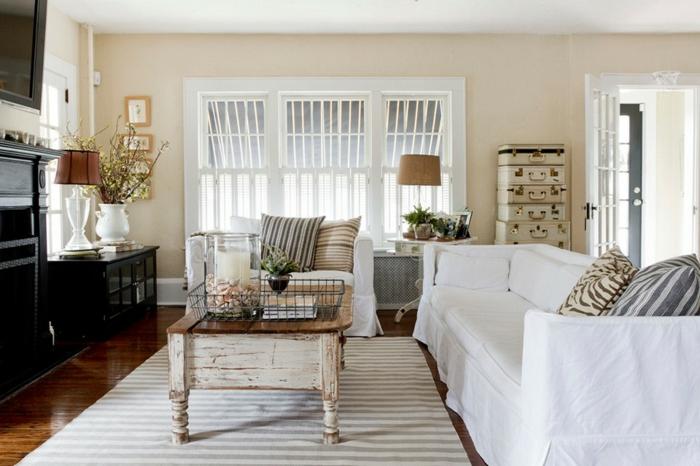landhausmöbel wohnzimmer, weißes sofa, schwarze schränke, vintage tisch im mittelpunkt des zimmers