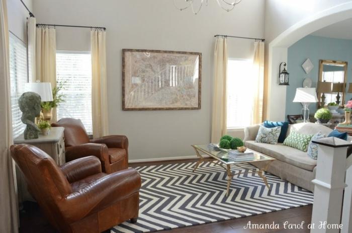 landhausmöbel wohnzimmer ledersessel in dunkelbraun, schwarz weißer teppich, sofa in beige glastisch, wandbild