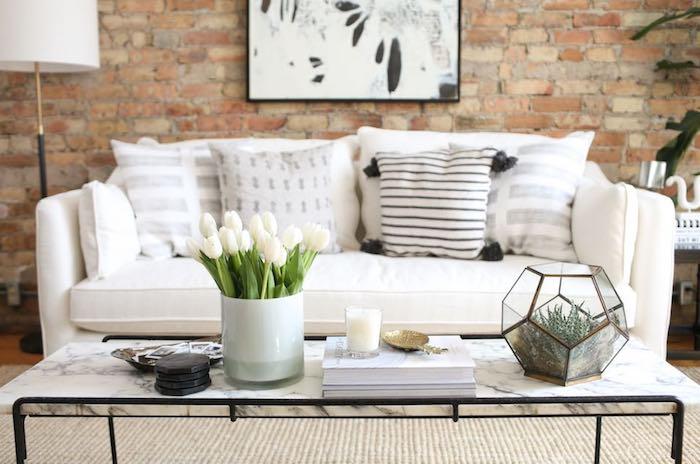 wohnzimmer deko ideen, weiße tulpen in große glasvase, zwei bücher, ziegelwand