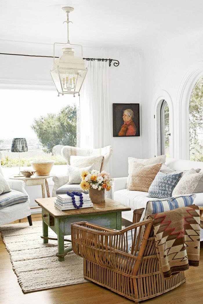 ein helles und breites wohnzimmer modern gestaltet, weiße farbe überwiegend, weiße wände, vintage tisch mit schublae, bild an der wand selbst gemalt, rattan sessel