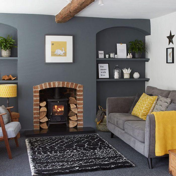 wohnzimmer grau weiß, kamin, regale mit dekorationen, graues sofa mit gelben dekokissen