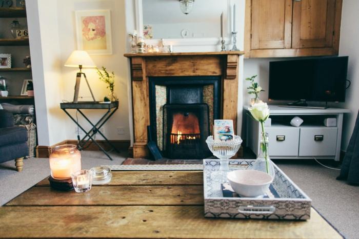 wohnzimmer im landhausstil designer idee, naturnahe deko und möbel, holztisch, holzmöbel, kamin, retro touch, tablett auf dem tisch, kerze, stehlampe, fernseher