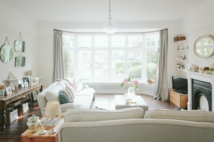 wohnzimmer im landhausstil weiße dekorationen, zwei weiße sofas, großes fenster, deko an der wand, spiegel