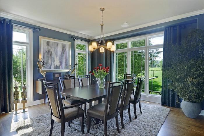 ein tisch aus holz und stühle aus holz, ein wohnzimmer mit einem boden aus holz und mit weißen fenstern mit blauen vorhängen und einer gelben lampe