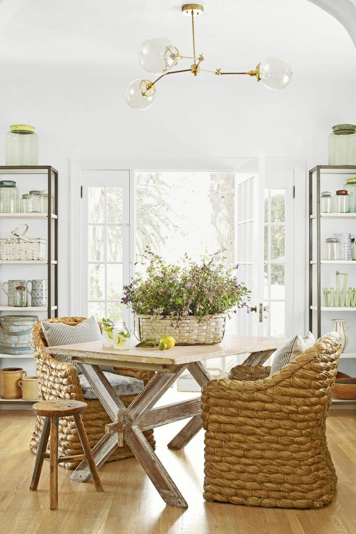 landhausmöbel designer ideen für ein gemütliches zuhause, zwei große stühle aus rattan und ein kleiner hocker, holztisch vintage, blumenkorb mit feldblumen