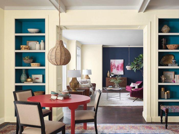 wohnzimmer mit einem roten kleinen tisch und mit drei braunen stühlen, ein zimmer mit einem braunen boden und zwei kleinen weißen lampen, blaue und weiße wände