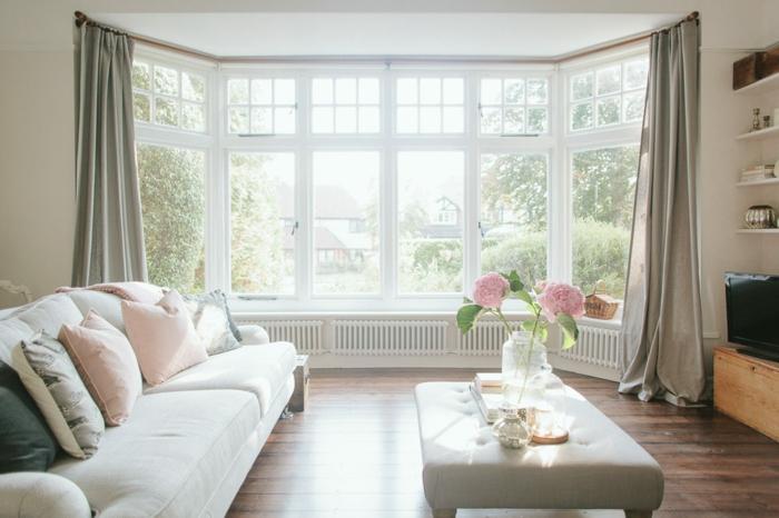 landhausmöbel idee, weißes zimmer, großes fenster mit hellen vorhängen, sofa mit vielen kissen, präzis gestaltetes zimmer, pinke blumen auf dem tisch